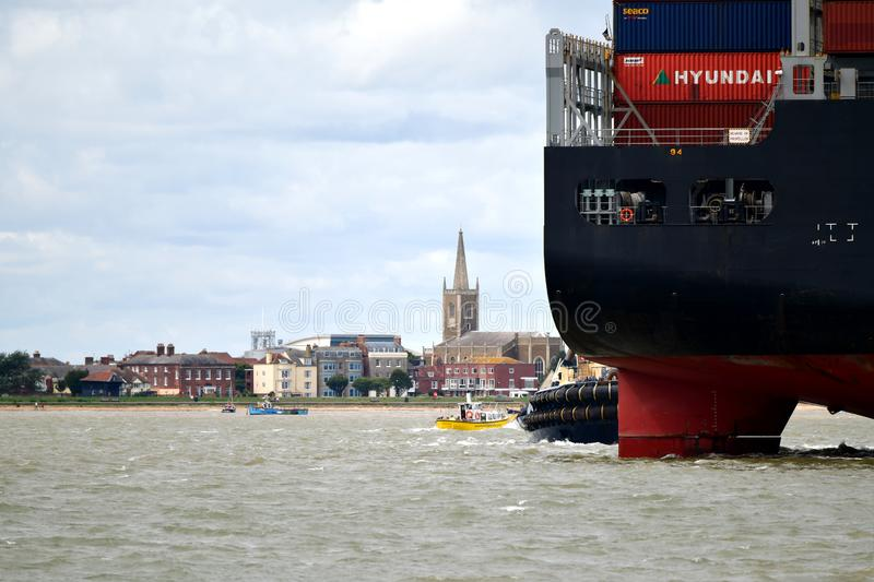 Tugs lead out a container ship from the port from Felixstowe UK. In the background a church tower and a city Tugs lead out a container ship from the port The royalty free stock image