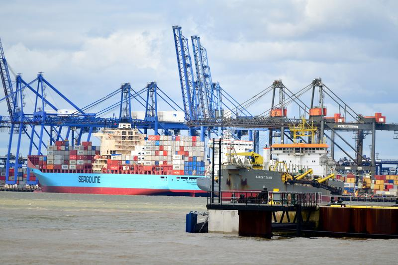 Port in Felixstowe UK. In the background a church tower and a city Tugs lead out a container ship from the port The Port of Felixstowe is Britain's stock image