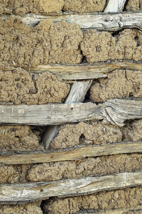Clay wall of straw and mud. Background close-up of the  wall of an ancient house made of mud mixed with straw royalty free stock photography