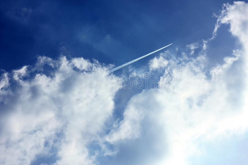 Cloudy blue sky jet trail. Background of cloudy blue sky with fighter aircraft fuel trace or jet trail royalty free stock images