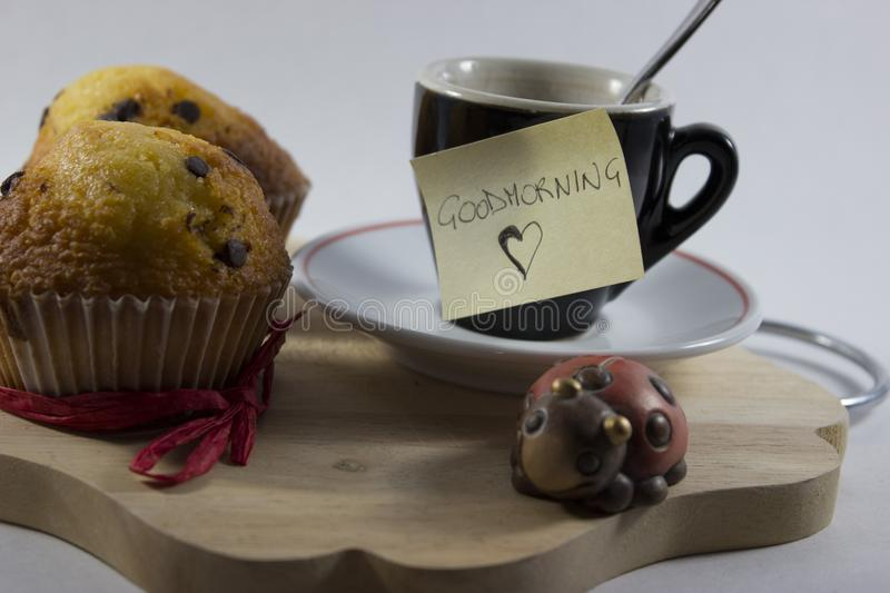background with coffee cup, two cakes, a ladybird and a good morning card royalty free stock photography