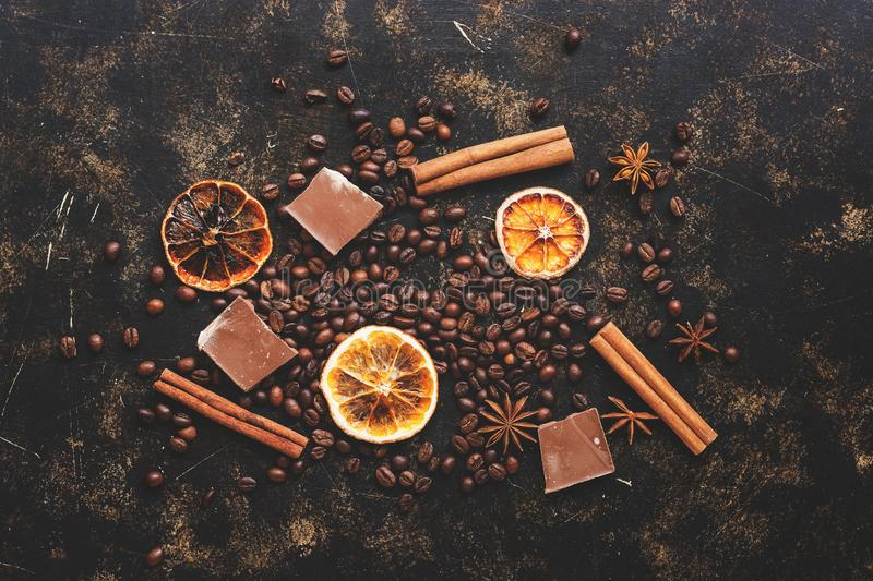 Background coffee grains, cinnamon sticks, star anise, orange slices and chocolate. Brown abstract background, top view, flat lay. royalty free stock photo