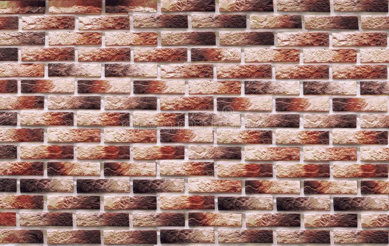 Background of colored clinker brick on the wall orange. Background of colored clinker bricks on the wall, which are used in the repair of premises stock photography