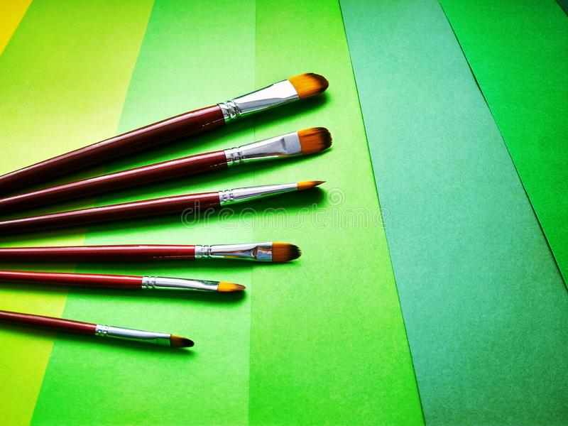 Paint brushes on a background of colored paper stock photo