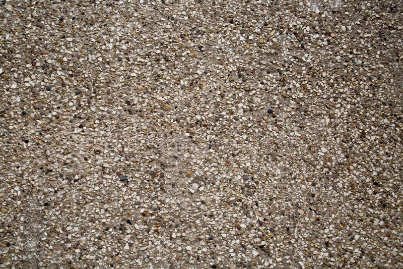 Background of concrete wall made of white gravel and colored pebbles stock photo