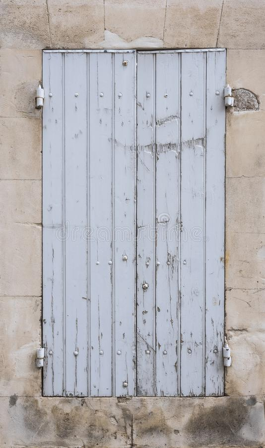 Light grey or white old shutters in limestone wall of french provence house stock image