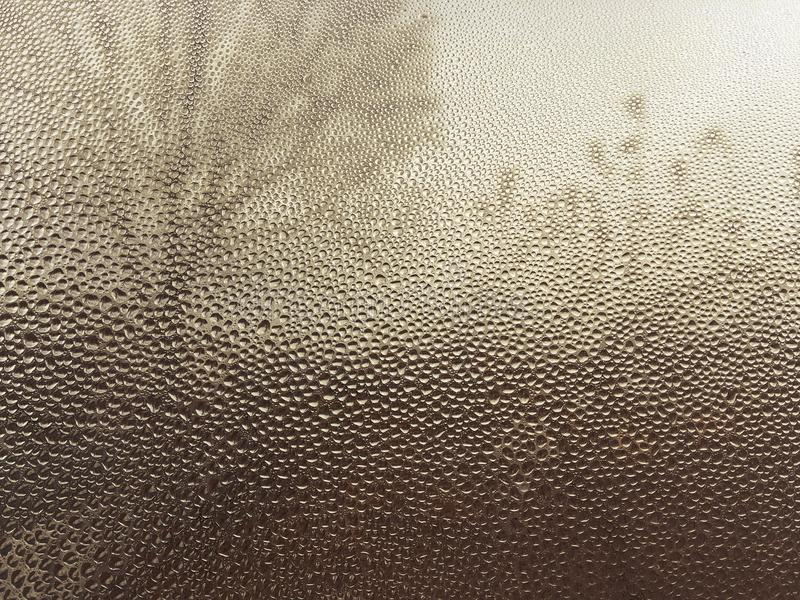 The glass covered with water drops through which the tree silhouette, a natural background in gold tones, volume drops of water on stock photos