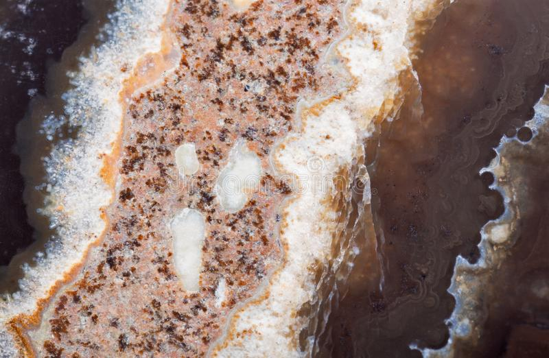 Light stripe in dark brown agate structure. Background with contrast agate structure stock photography