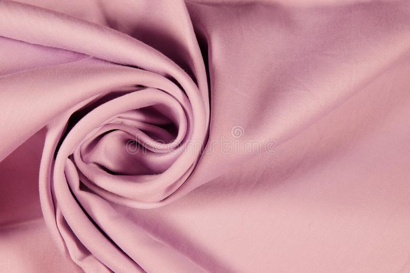 Beautiful draped silk satin. close up of pink Fabric for a decor by decorative spiral folds. royalty free stock photo