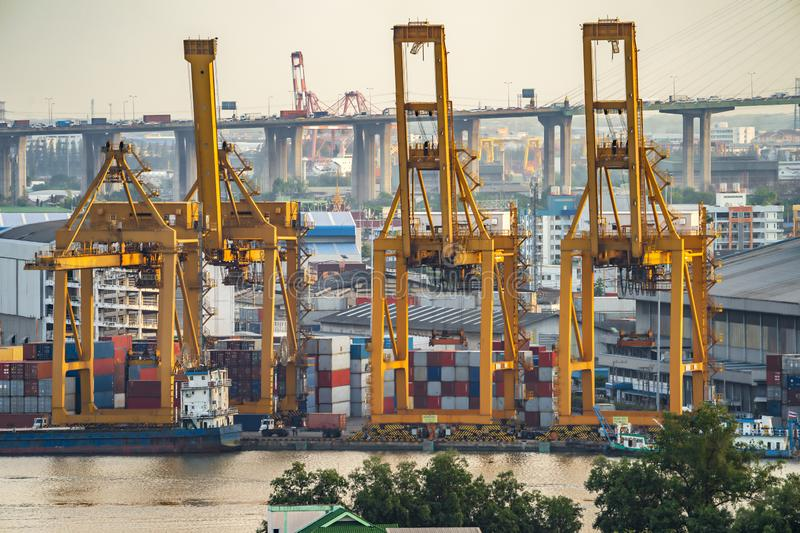 Background for cranes and industrial cargo ships in port at twilight royalty free stock photos
