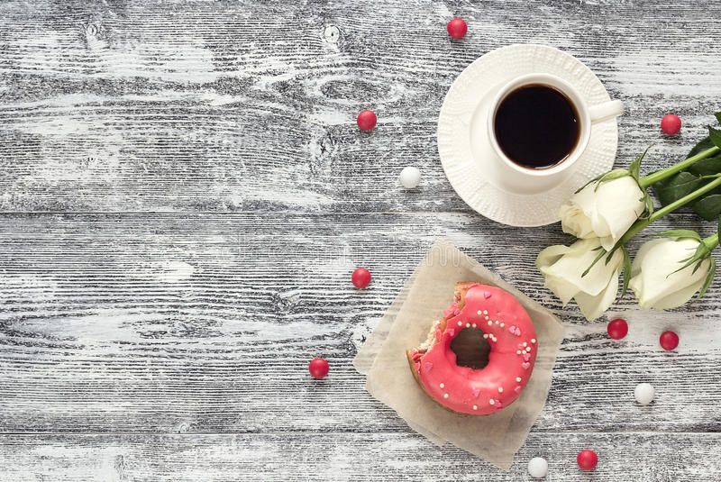 Background with cup of coffee, donut and white roses on a gray. Wooden table. Top view with copy space stock images