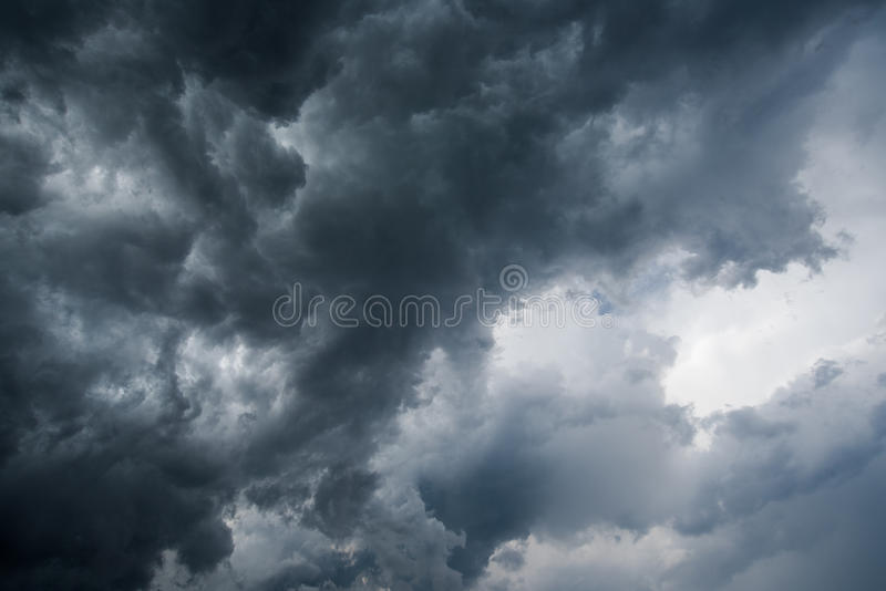 Background of dark clouds before a thunder-storm ,sunlight through very dark clouds background ,White Hole in the Whirlwind of dar. K storm clouds stock image
