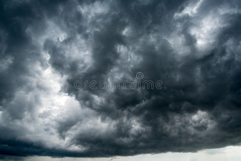 Background of dark clouds before a thunder-storm ,sunlight through very dark clouds background ,White Hole in the Whirlwind of dar. K storm clouds royalty free stock images