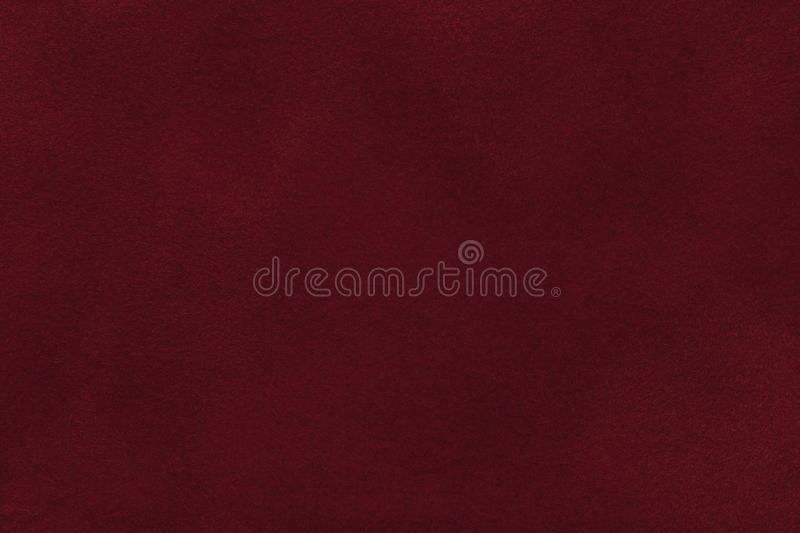 Background of dark red suede fabric closeup. Velvet matt texture of wine nubuck textile royalty free stock image