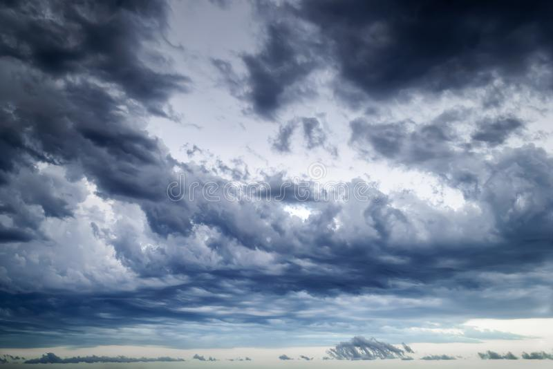 Background of dark stormy sky at summer evening. Dramatic skyscape with large gray clouds. Atmospheric phenomena stock photography