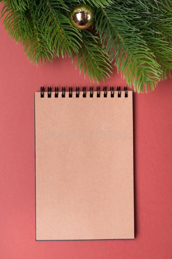 Background with decorated fir tree and blank notebook list in the middle. Top view with copy space. New year concept. Christmas concept. Winter concept stock image