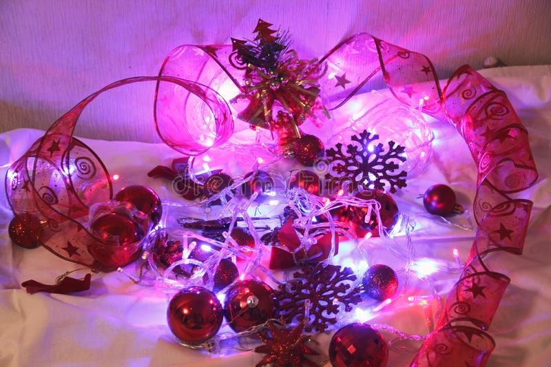 Christmas and Valentin background is decorated with lights of garlands, sparkling red balls, snowflake and decorative. Background is decorated with lights of stock photo