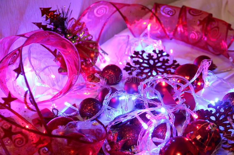 Christmas and valentinbackground is decorated with lights of garlands, sparkling red balls, snowflake and decorative. Background is decorated with lights of stock image
