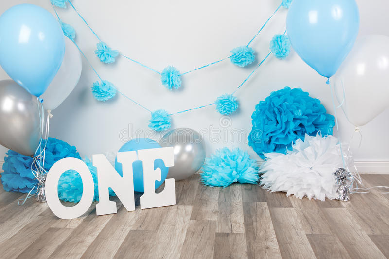 Background decoration for birthday celebration with gourmet cake, letters saying one and blue balloons in studio. Festive background decoration for birthday royalty free stock images