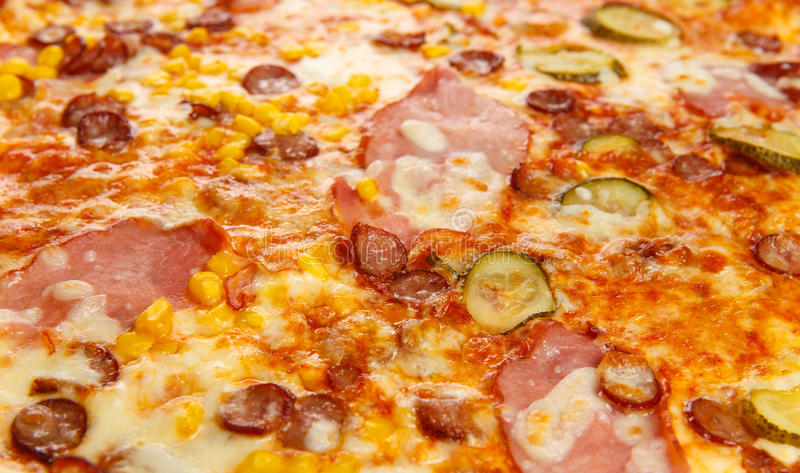 Background of delicious classic italian pizza with ham, sausages, corn, cucumbers and cheese stock photography