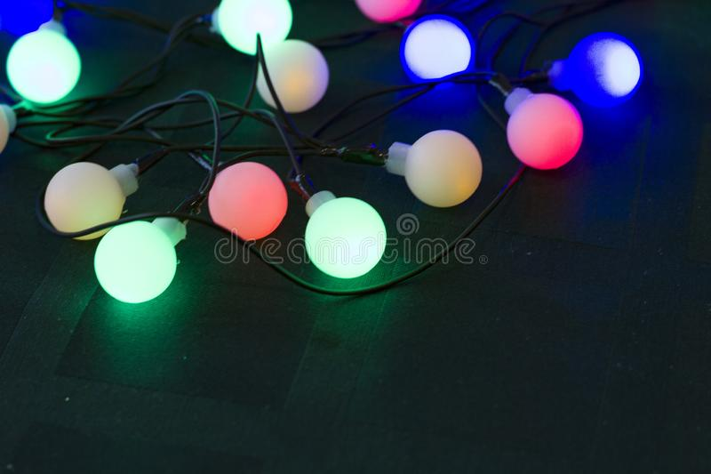 Happy New Year 2020. Christmas decorations on a dark green background with burning garland lights royalty free stock photography