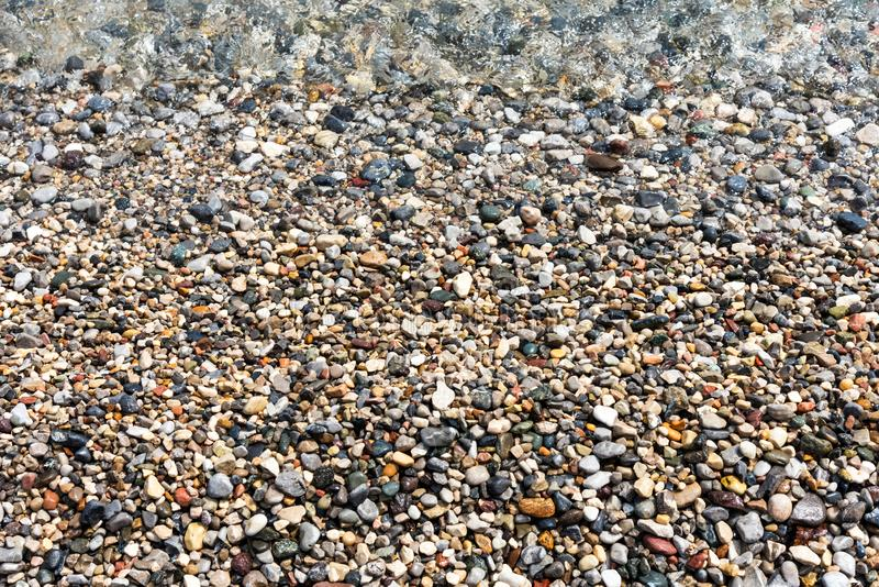 Background of different sizes and colors of wet sea pebbles, stones and water stock image