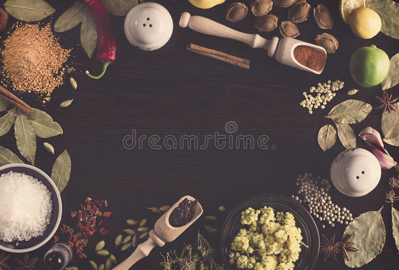 Background different spices on the table such as coconut, ground pepper in a spoon for spices, Hypericum, turmeric, bay leaves, co. Vintage horizontal background royalty free stock images