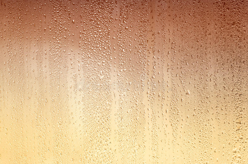 Background with drops on glass, stained yellow-brown. Plenty of space for text royalty free stock images