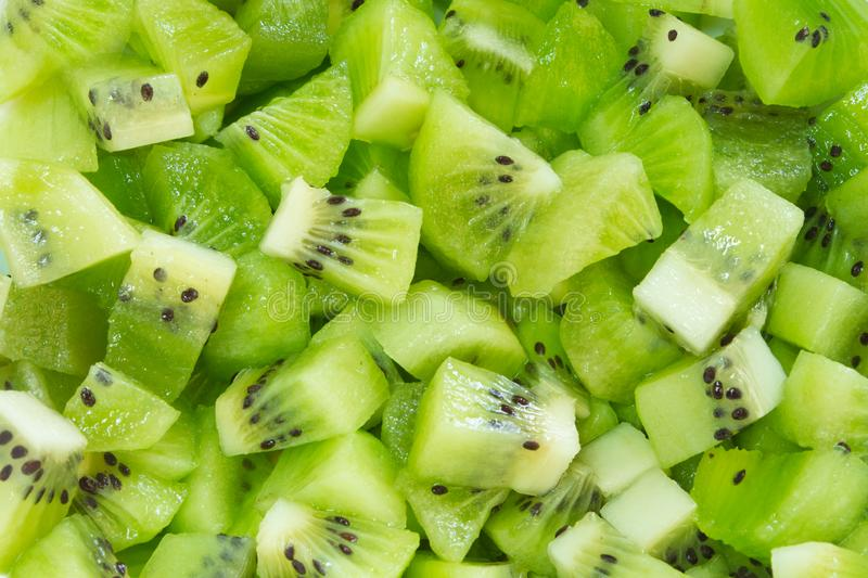 Background of finely chopped pieces of juicy kiwi with seeds without peel royalty free stock photos