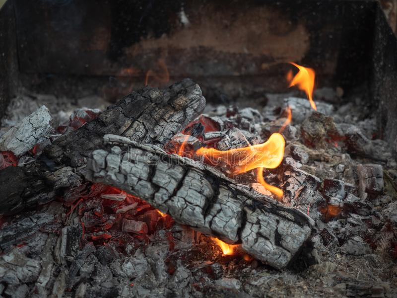 Background of fireplace with gloving embers. Close up view on smouldering fire. Embers burning with red and yellow flame stock image