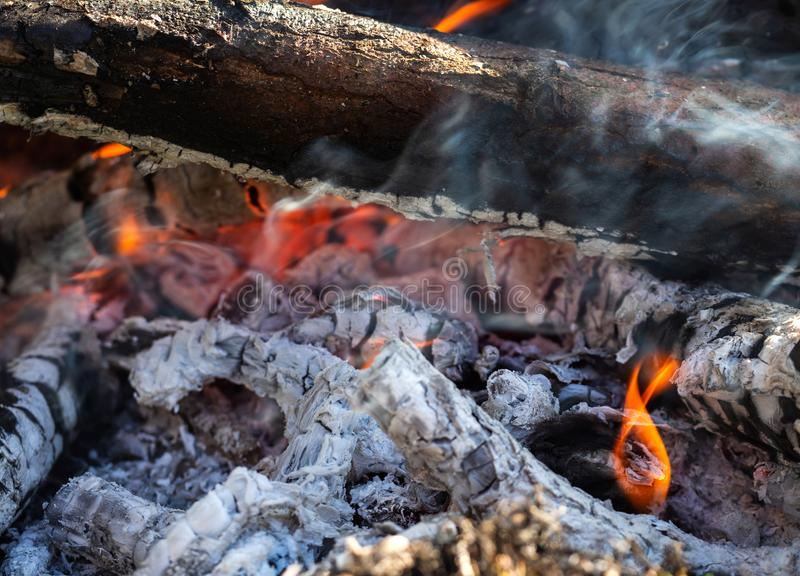 Background of fireplace with gloving embers. Macro shot of smouldering fire. Embers burning with red flame. Texture of ash and royalty free stock image