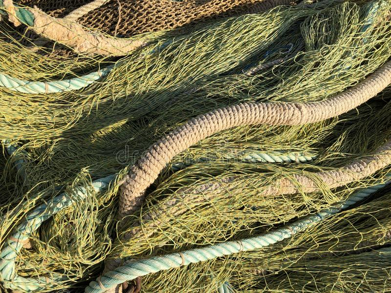 Background. Fishing nets drying in the sun. Javea, Alicante / Spain abstract pattern of green nets drying in a heap on the quayside stock photography