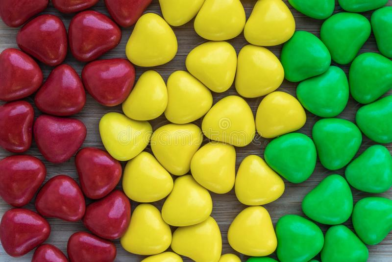 Background in the form of hearts of milk chocolate, covered with multi-colored glaze of red, yellow and green stock image