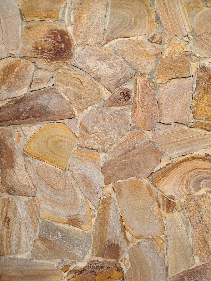 Background in the form of a stone wall made of many flat buta stones of light brown color. Brown stone fence, cement, construction, rough, surface, texture stock image