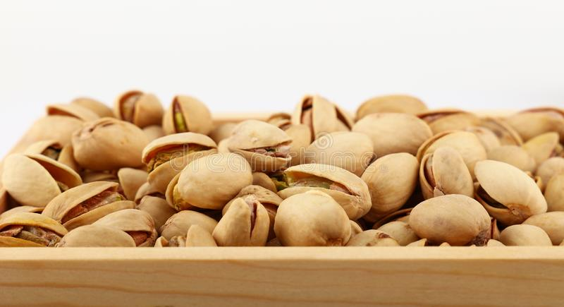 Background of fresh roasted pistachio nuts. Close up fresh roasted pistachio nuts in wooden box over white background, low angle view stock photo