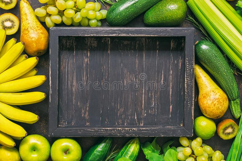 Background of fresh vegetables and fruits with an empty wooden tray. Frame of yellow and green vegetables. A top view, a place for royalty free stock images