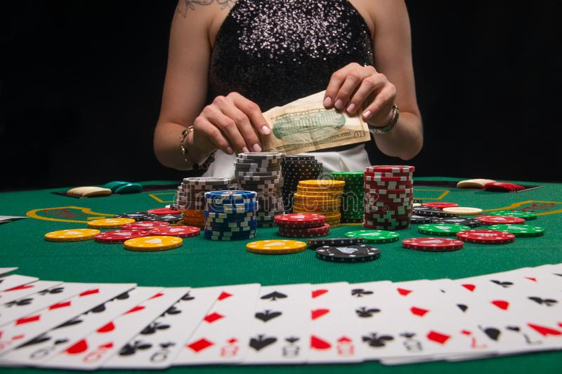 Background of a gaming casino, poker table, cards, chips and a girl with a glass of wine in the background. Background for a. Gaming business, success stock photos