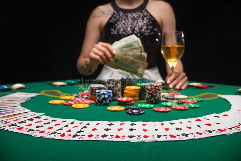 Background of a gaming casino, poker table, cards, chips and a girl with a glass of wine in the background. Background for a. Gaming business, success royalty free stock photo