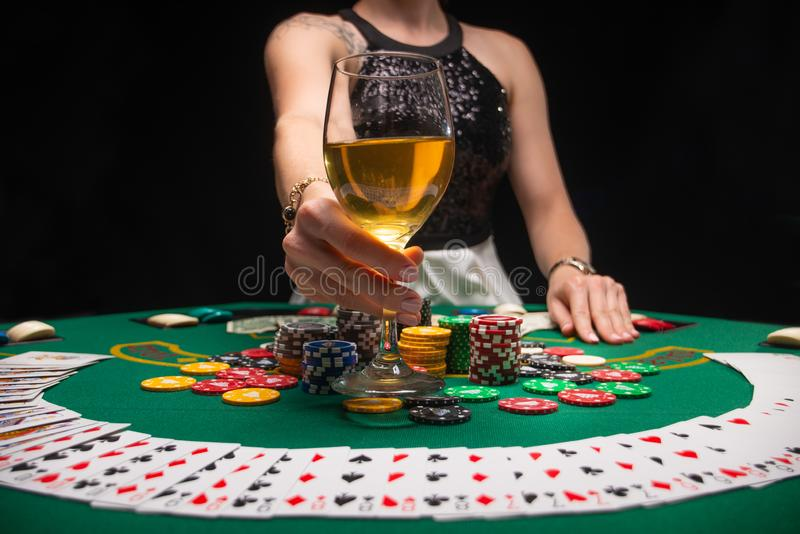 Background of a gaming casino, poker table, cards, chips and a girl with a glass of wine and smoke. Background for a gaming. Business, success, horizontal photo stock photography
