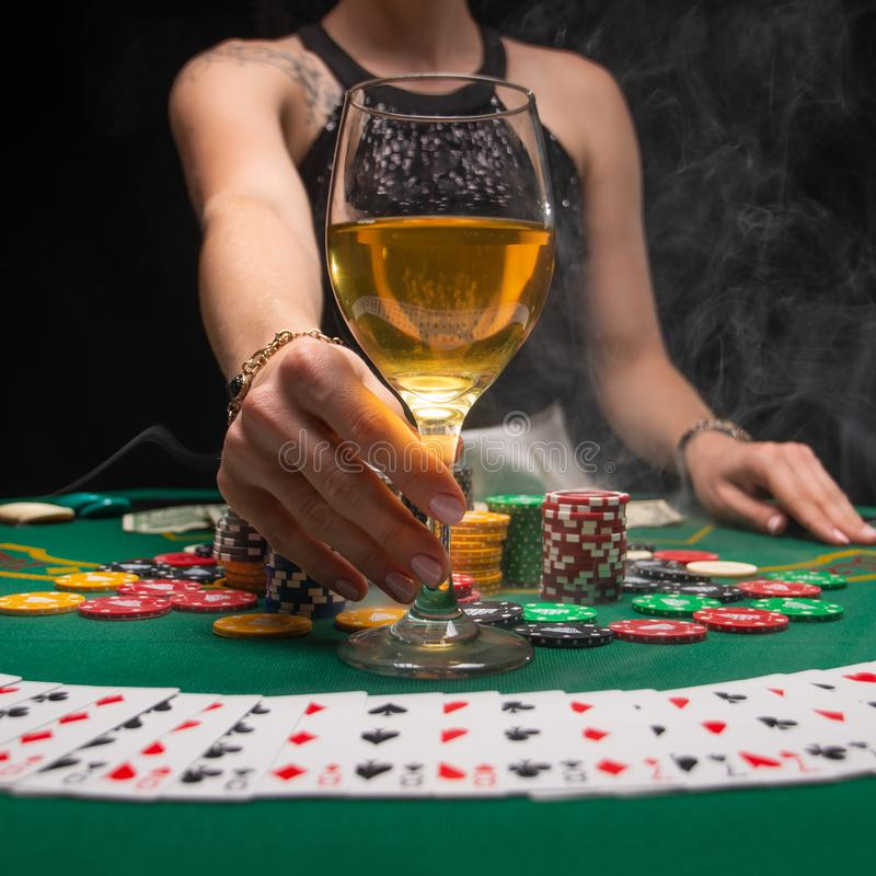 Background of a gaming casino, poker table, cards, chips and a girl with a glass of wine and smoke. Background for a gaming. Business, success, square photo royalty free stock image