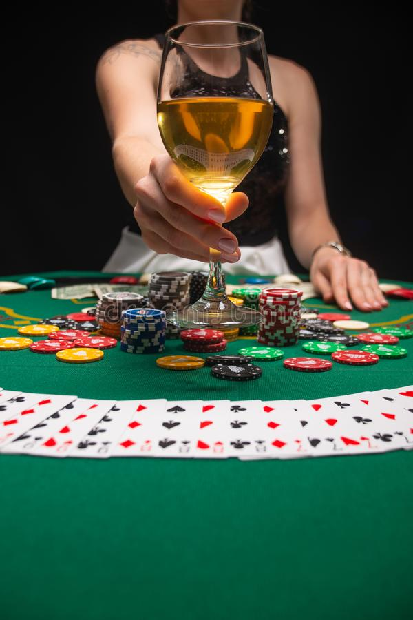 Background of a gaming casino, poker tables, cards, chips and a girl with a glass of wine. Background for a gaming business,. Success, Vertical photo royalty free stock photography