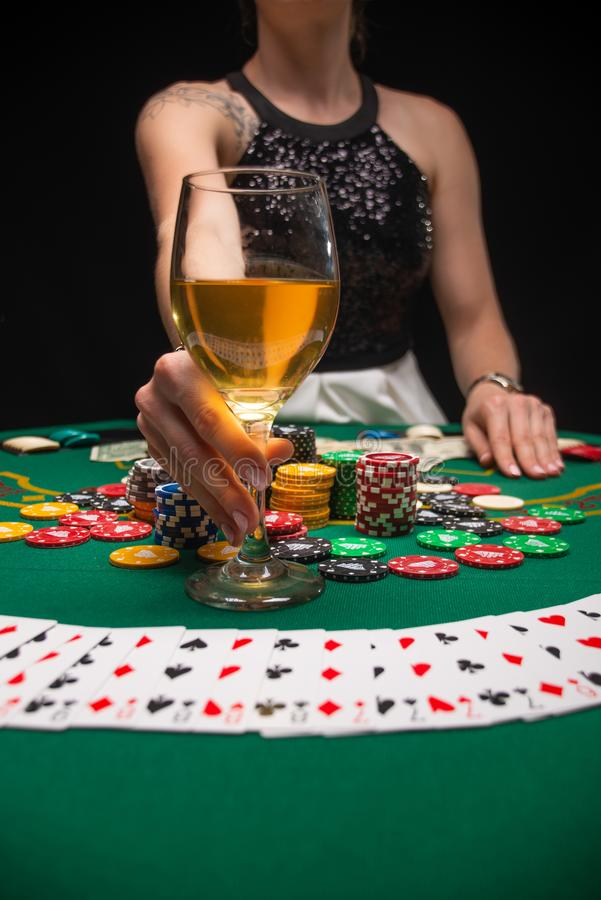 Background of a gaming casino, poker tables, cards, chips and a girl with a glass of wine. Background for a gaming business,. Success, Vertical photo stock photo