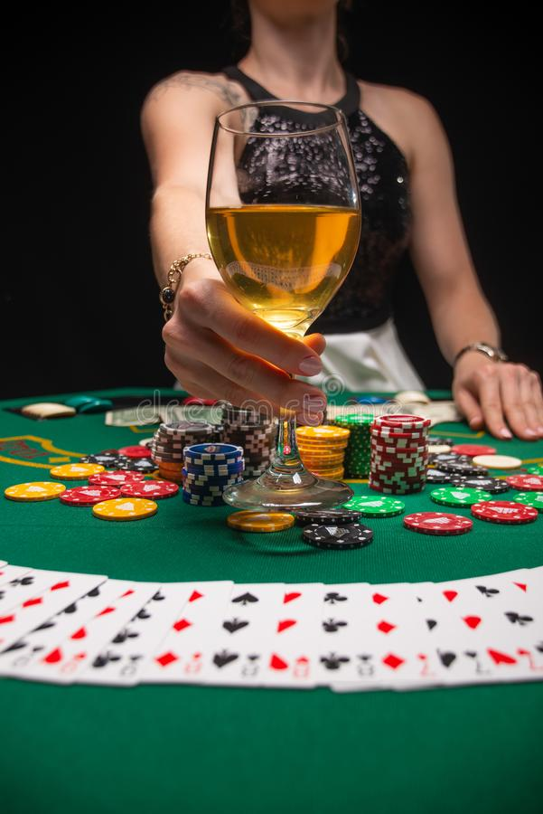 Background of a gaming casino, poker tables, cards, chips and a girl with a glass of wine. Background for a gaming business,. Success, Vertical photo stock image
