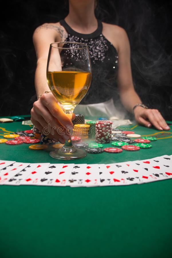 Background of a gaming casino, poker tables, cards, chips and a girl with a glass of wine and smoke. Background for a gaming. Business, success, Vertical photo royalty free stock image