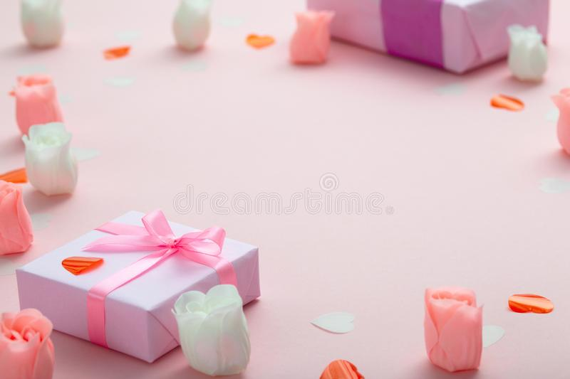 Background of gifts with confetti hearts and roses, boxes wrapped in decorative paper on pastel colored pink background, holiday stock photos