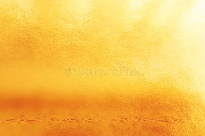 Background of gold foil texture with light reflections.  royalty free stock photo