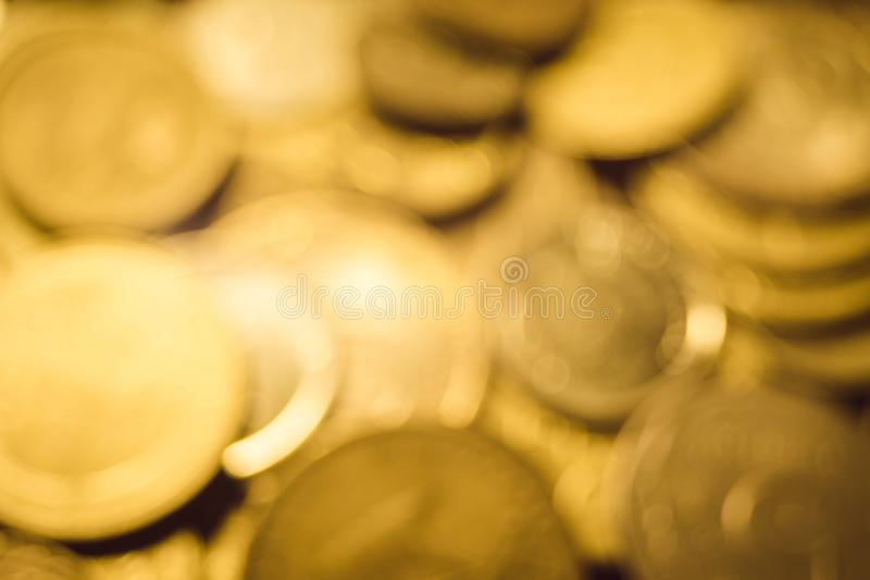 Background golden pile of different gold coins on the table, blurred unfocused photo royalty free stock photography
