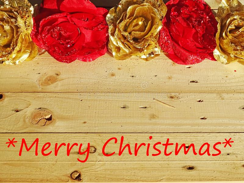 Background of golden and red flowers with text Merry Christmas. Wooden background with golden and red flowers with tekst Merry Christmas stock photos