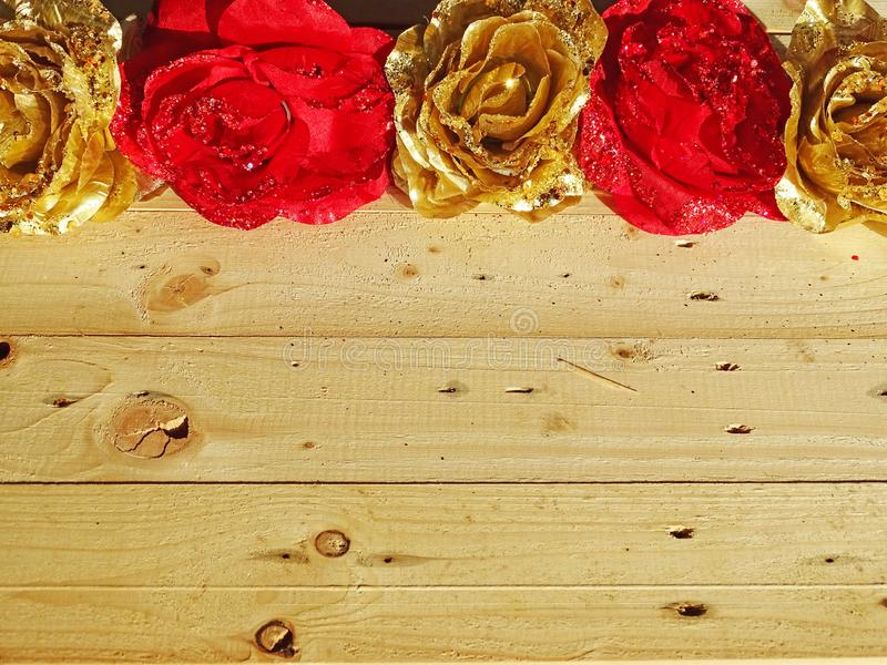 Background of golden and red flowers. Wooden background with golden and red flowers royalty free stock image