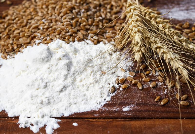 Background of Golden wheat grains with ears and white crumbling flour scattered on wooden table stock photos